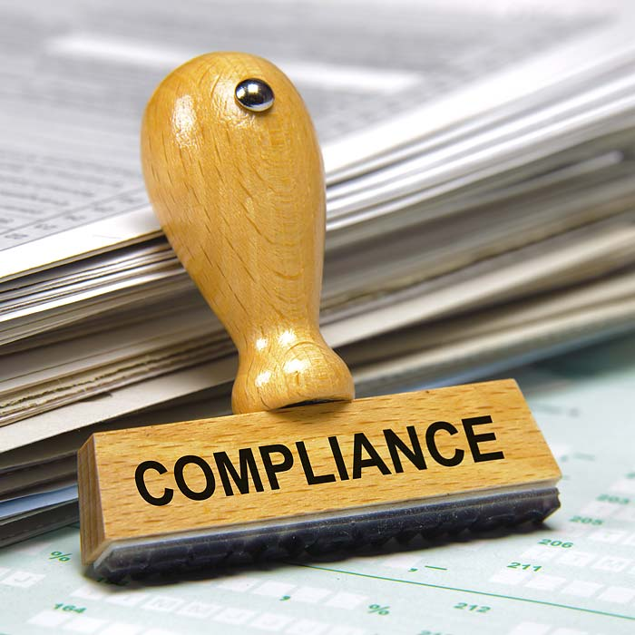 Wooden Compliance Rubber Stamp Against Stack Of Papers