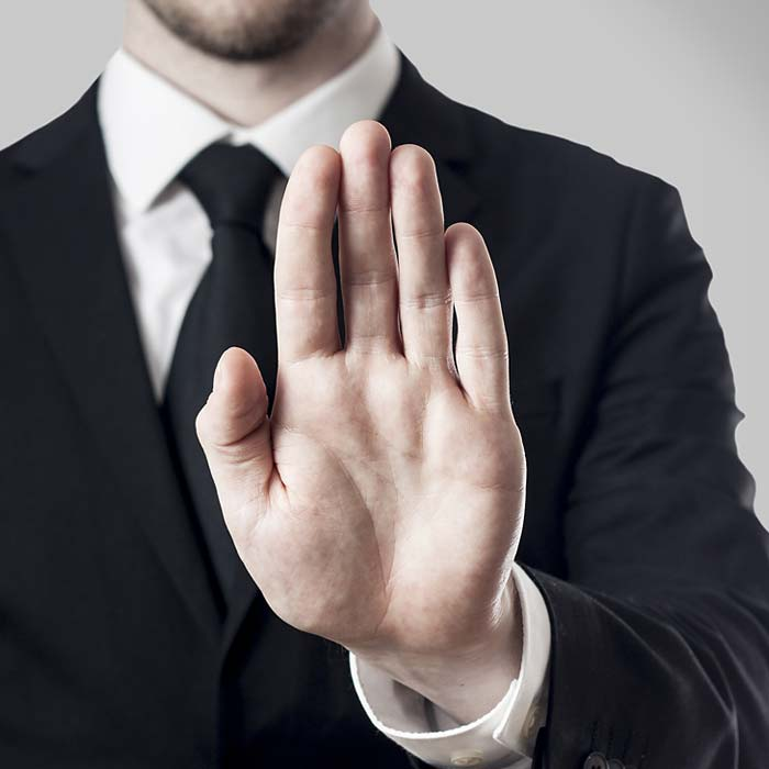 Man In A Black Suit With His Hand Held Up In A Stop Gesture