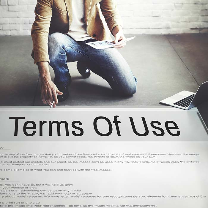Man Bent Down Looking At Terms Of Use Poster On Floor