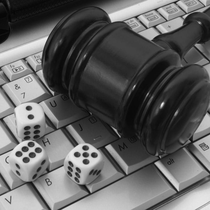 Online gambling and law theme with gavel and dice on keyboard